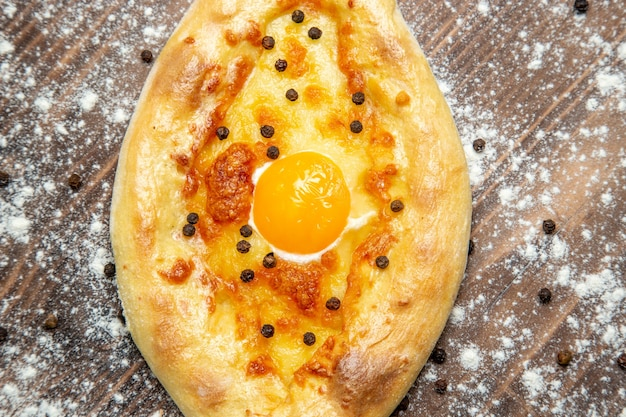 Pão fresco assado com ovo cozido e farinha em uma mesa marrom