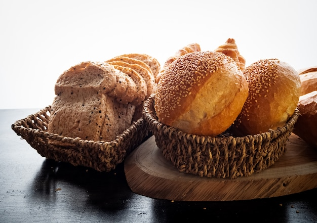 Pão fresco assado e baguete em fundo de madeira