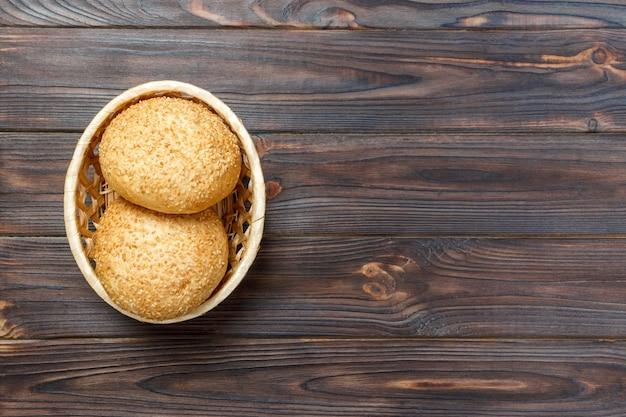 Pão fresco caseiro em uma cesta na velha mesa de madeira