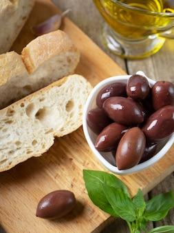Pão fresco ciabatta e azeite grego preto aromático com ervas e especiarias em uma tábua de madeira
