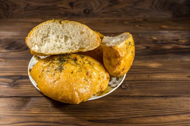 Pão fresco ciabatta em um prato na mesa de madeira
