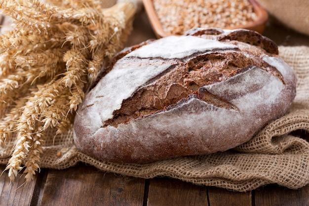Pão fresco com espigas de trigo na mesa de madeira