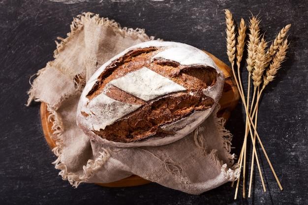 Pão fresco com espigas de trigo na mesa escura, vista superior
