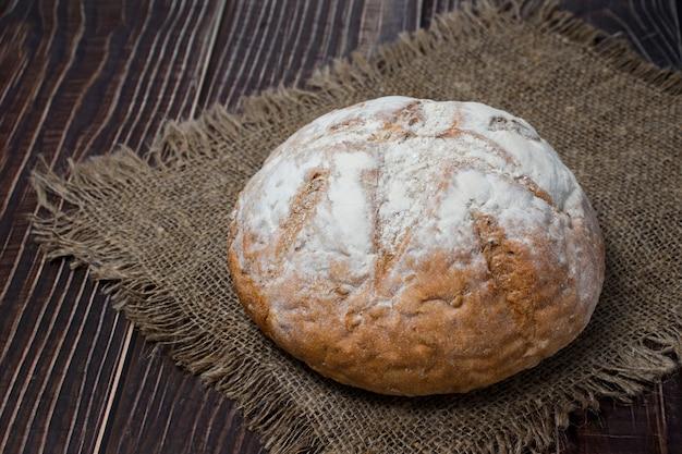 Pão fresco com farinha sobre um pano sobre uma mesa de madeira escura