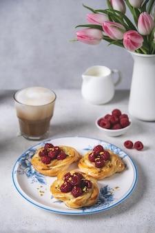 Pão fresco com framboesas e café cappuccino na mesa branca