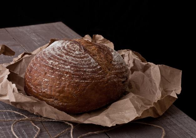 Pão fresco com papel pardo na placa de madeira