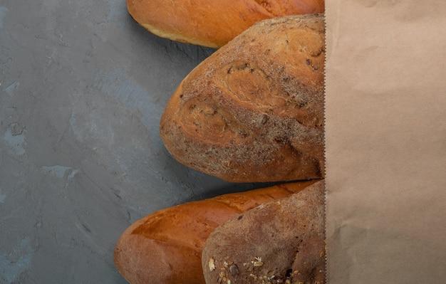 Pão fresco e baguete em um saco de papel em um fundo cinza textural.