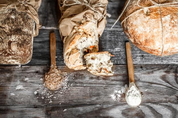Pão fresco e colher de pau na mesa de madeira velha