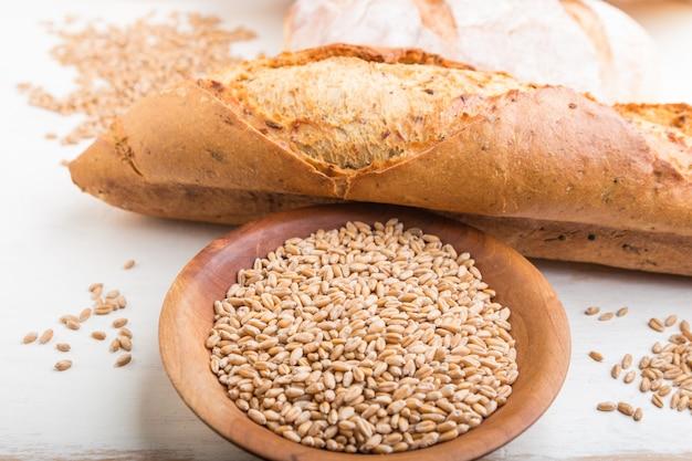 Pão fresco e placa de madeira com sementes de trigo no fundo branco de madeira