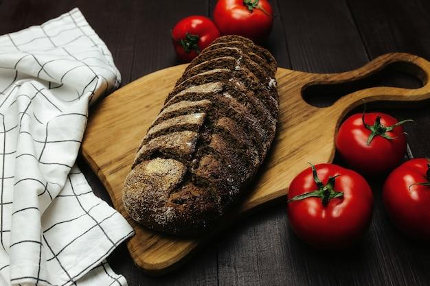 Pão fresco e tomate na mesa de madeira. foto de alta qualidade