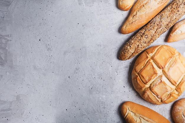 Pão fresco em um fundo cinza de concreto. vista superior com espaço de cópia