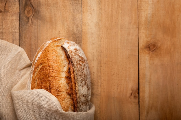 Pão fresco em uma mesa de madeira em um guardanapo. vista superior com espaço de cópia.