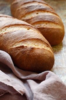 Pão fresco em uma parede marrom. trigo tradicional pão cozido rústico, naco de pão.