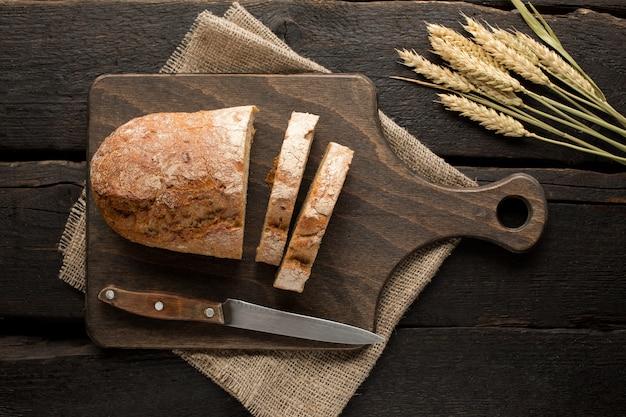Pão fresco em uma placa com trigo na madeira
