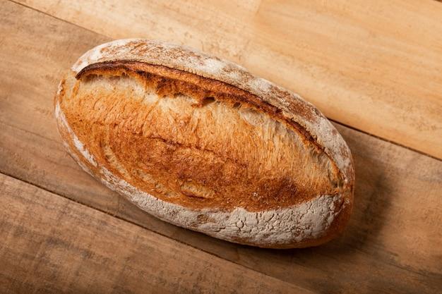 Pão fresco em uma tabela de madeira da prancha do vintage velho.