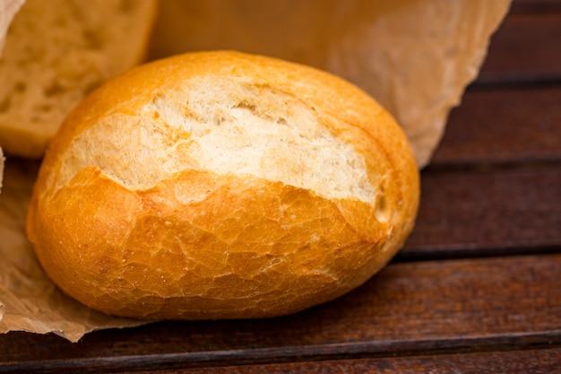 Pão fresco embrulhado em papel, sobre fundo de madeira.