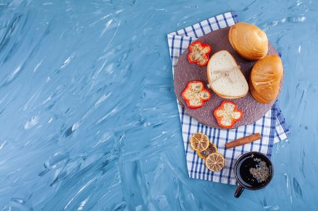 Pão fresco fatiado e xícara de chá quente na superfície azul.