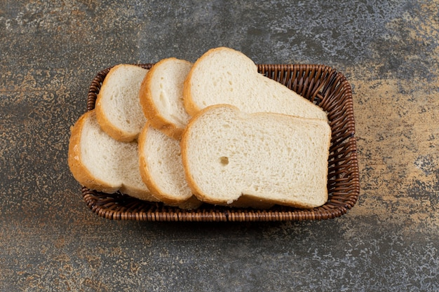 Pão fresco fatiado em cesta de madeira