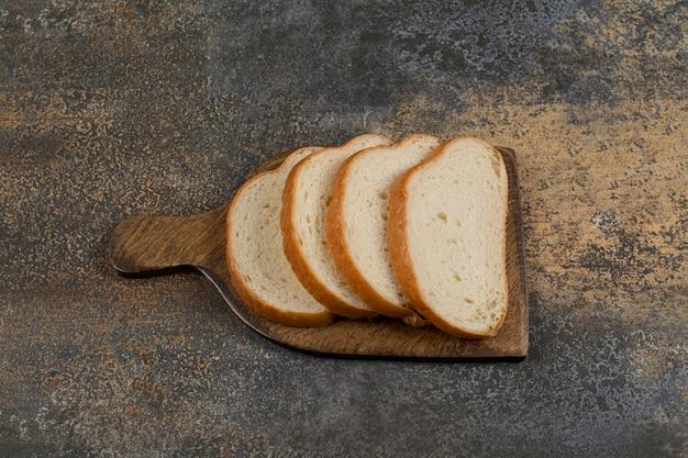 Pão fresco fatiado em tábua de madeira