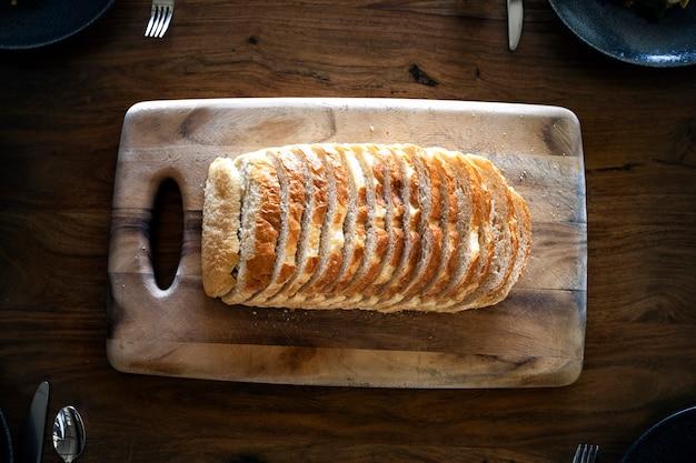 Pão fresco fatiado em uma tábua de madeira