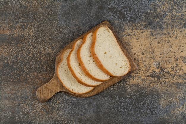 Pão fresco fatiado na placa de madeira.