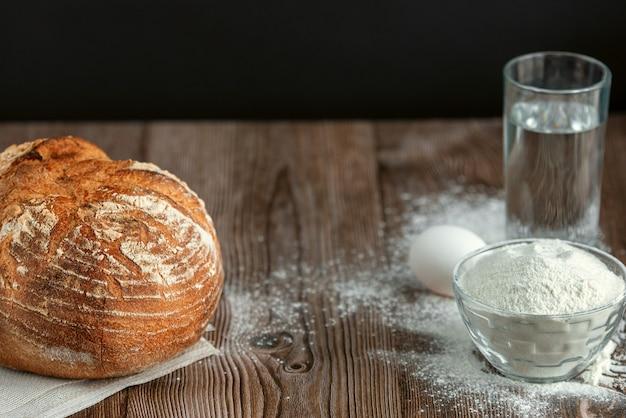 Pão fresco grande redondo na mesa de madeira closeup pão fresco na cozinha