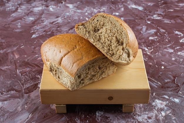 Pão fresco marrom picado em uma placa de madeira.