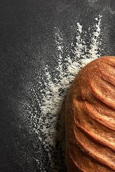 Pão fresco orgânico com um padrão de farinha apresentado em um fundo preto com espaço para texto. vista do topo