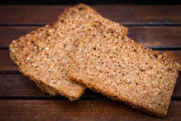 Pão fresco ou bolo com gergelim em fundo de madeira.