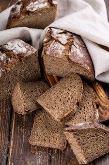 Pão fresco quente cortado em pedaços em uma velha tábua de madeira, com guardanapo, vertical