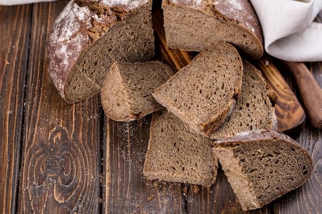 Pão fresco quente cortado em pedaços em uma velha tábua de madeira, horizontal