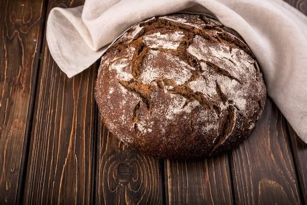 Pão fresco redondo e quente na velha mesa de madeira com guardanapo horizontal