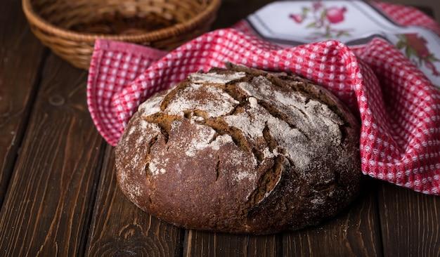 Pão fresco redondo e quente na velha mesa de madeira com guardanapo vermelho, horizontal