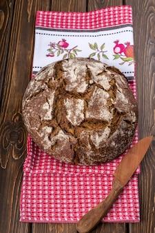 Pão fresco redondo e quente na velha mesa de madeira e guardanapo vermelho
