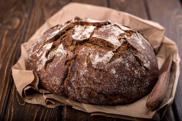 Pão fresco redondo e quente na velha mesa de madeira e no papel, horizontal
