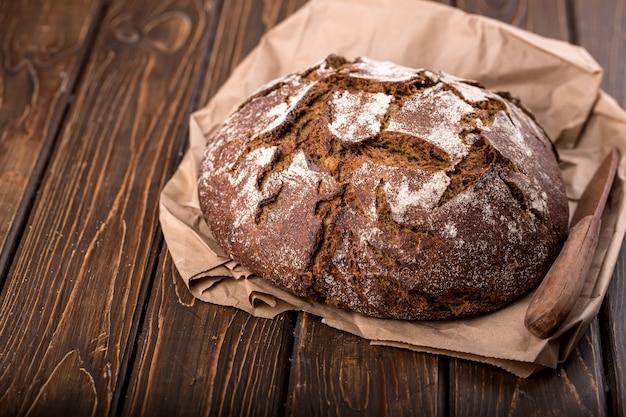 Pão fresco redondo e quente na velha mesa de madeira e no papel