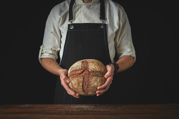 Pão fresco redondo feito de farinha de centeio, mãos masculinas segurando um fundo escuro