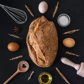 Pão fresco rodeado por vários ingredientes e utensílios de cozimento em pano de fundo preto