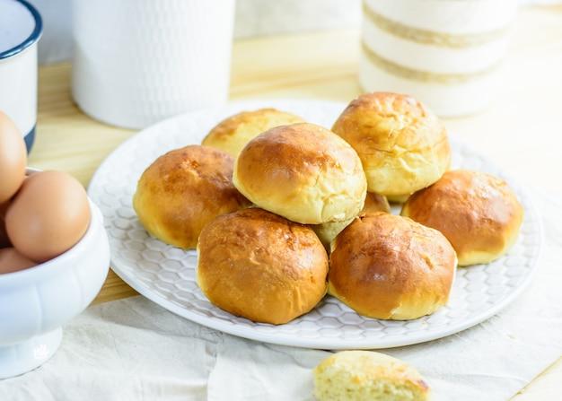 Pão fresco, utensílios de cozinha e ovos em fundo de madeira, padaria caseira