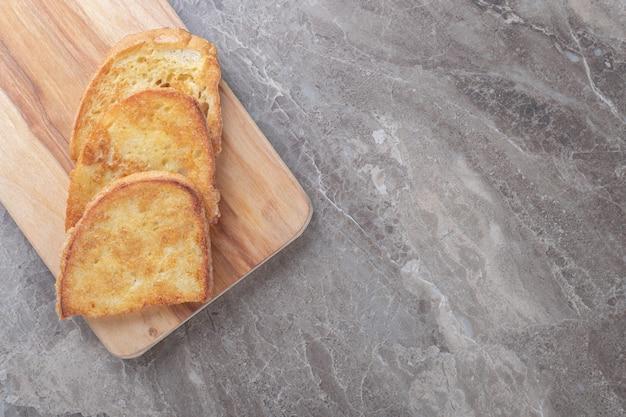 Pão frito com ovo na placa de madeira.