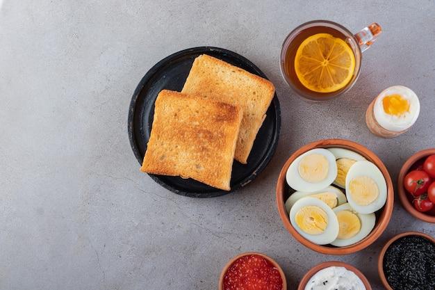 Pão frito com uma xícara de chá preto e ovos cozidos.
