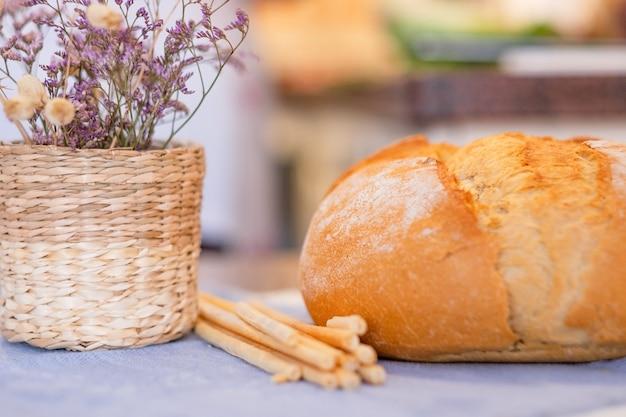 Pão grande na mesa de casa. palitos de pão, cesta de flores secas