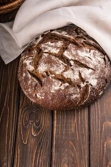 Pão integral acabado de cozer na mesa de madeira com guardanapo vertical