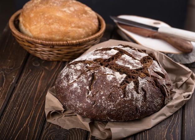 Pão integral acabado de fazer e quente na velha tábua de madeira e papel, horizontal