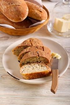 Pão integral caseiro com sementes misturadas fatiado e servido com manteiga