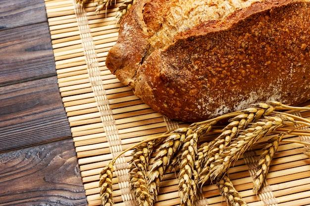 Pão integral caseiro fresco com trigo em um fundo de madeira