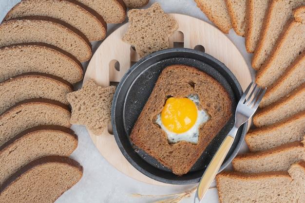 Pão integral com ovo frito na frigideira escura.