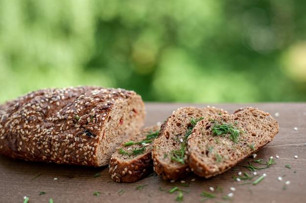 Pão integral com sementes de gergelim, cortado em pedaços e polvilhado com endro em uma placa de madeira na natureza.