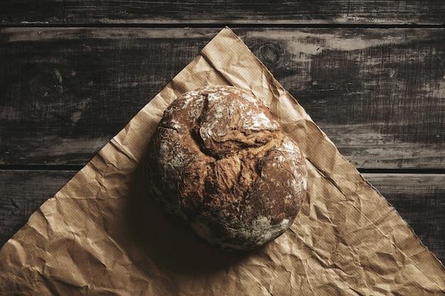 Pão integral de centeio saudável redondo em papel artesanal marrom, isolado na mesa de madeira preta da fazenda.