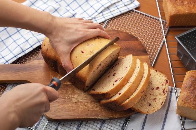 Pão integral de cranberry com corte de mão de mulher